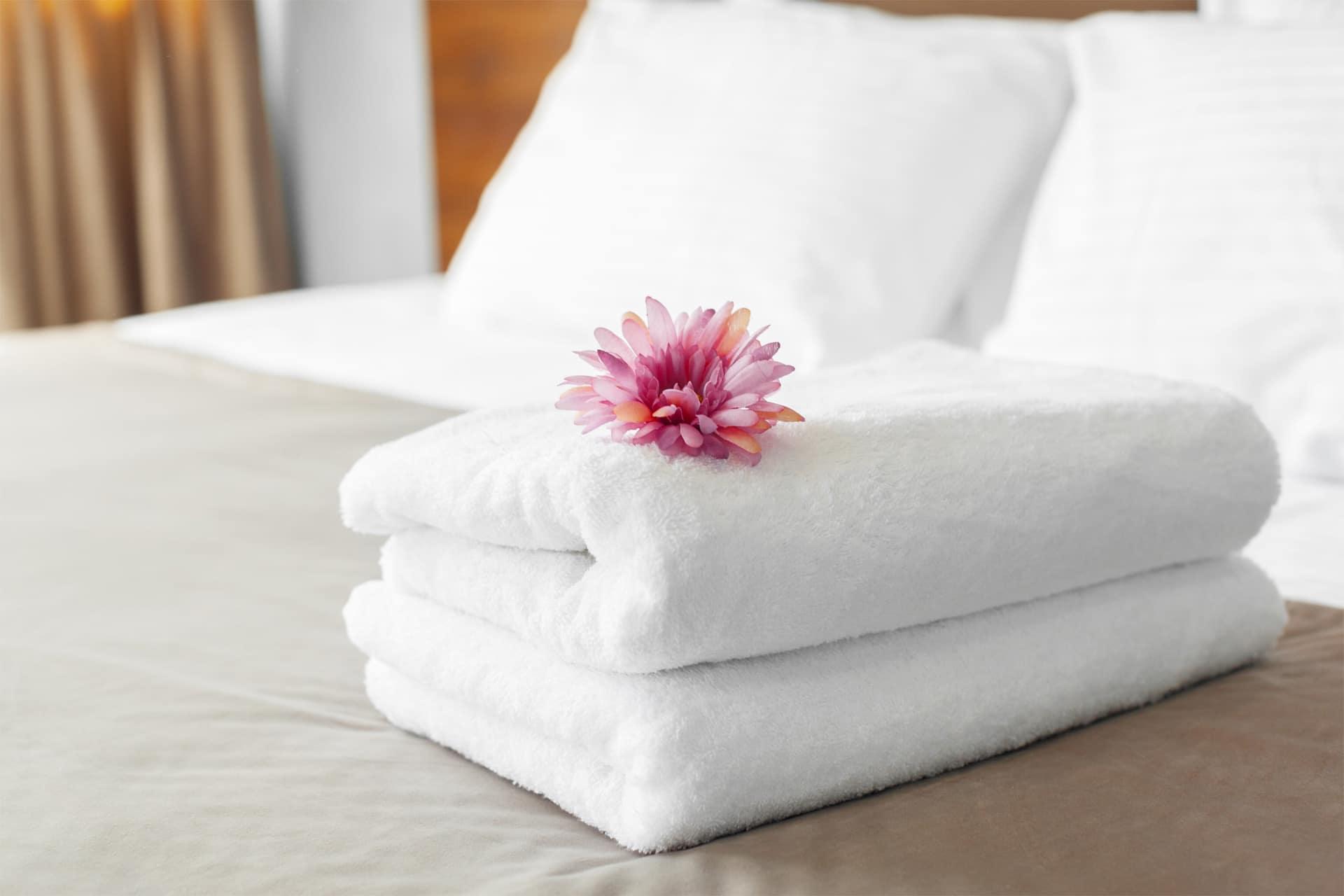 Ein Hotelbett mit weißen Handtüchern, die darauf liegen. Eine rosane Blume dient als dekoratives Element.