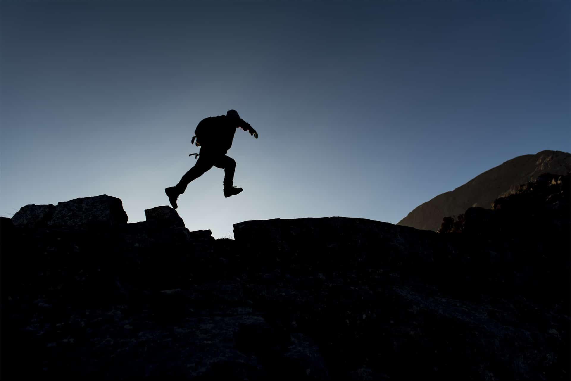 Nachtaufnahme von einem Wanderer, der auf einem Felsen steht und springt