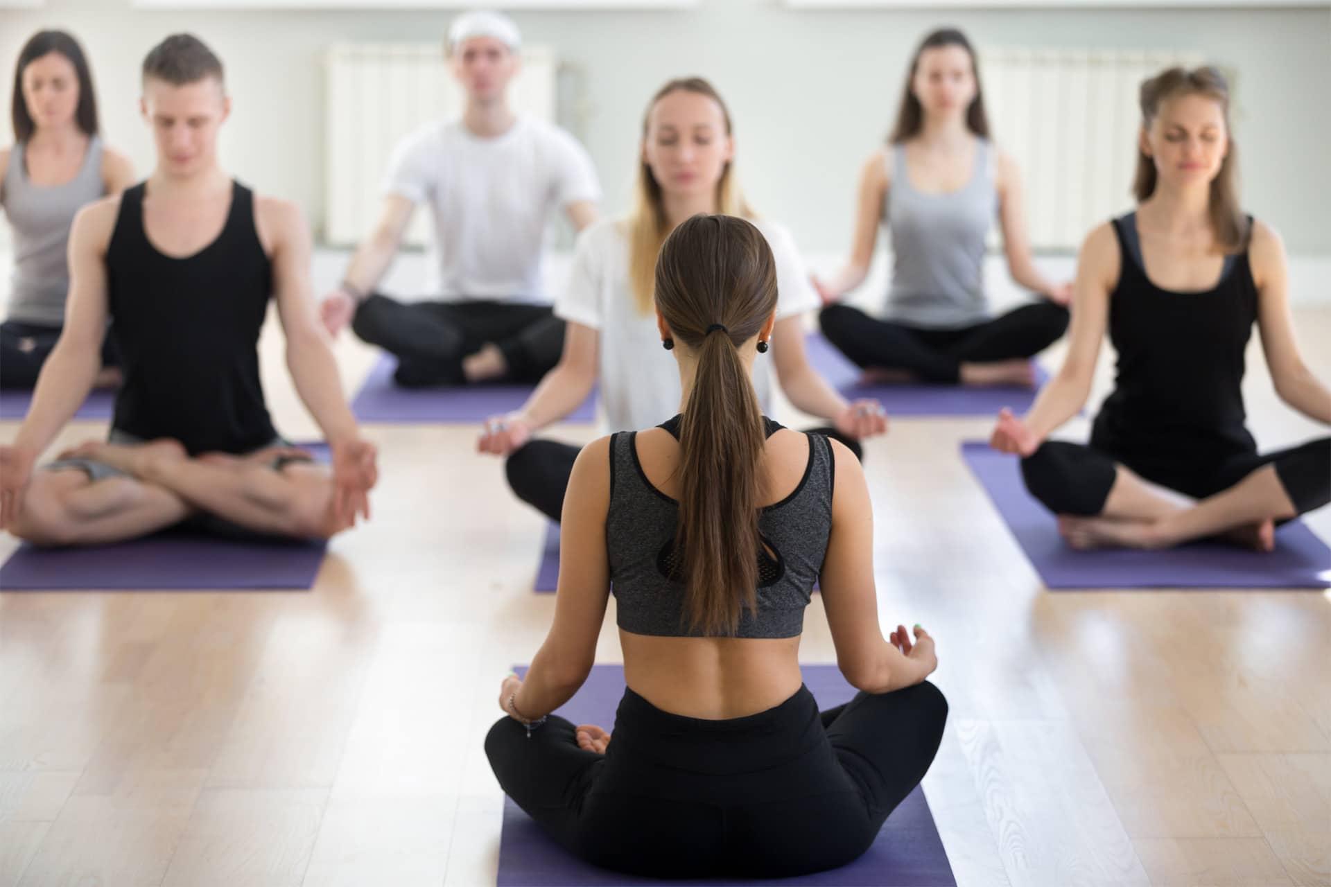 Eine Yogalehrerin, die vor Kursteilnehmer*innen eine Yogastunde abhält